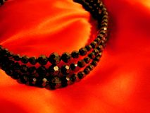 Black bead jewelry necklace on red satin background for valentines day Royalty Free Stock Photos