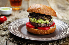 Black bean burger with mashed avocado, caramelized onions and to Stock Photos