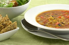 Black bean and corn soup. With caesar salad and crispy crackers royalty free stock photography