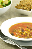 Black bean and corn soup. With caesar salad and crispy crackers royalty free stock photo