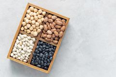 Black beans, pinto beans, white beans and chickpeas in a wooden box on concrete background, copy space, horizontal. Black beans, pinto beans, white beans and stock image