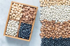 Black beans, pinto beans, white beans and chickpeas in wooden box and on concrete background, flat lay, horizontal. Black beans, pinto beans, white beans and stock photography