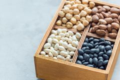 Black beans, pinto beans, white beans and chickpeas in wooden box on concrete background, copy space, horizontal. Black beans, pinto beans, white beans and stock photography