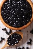 Black beans in a wooden spoon and a bowl macro. vertical top vie Royalty Free Stock Photos