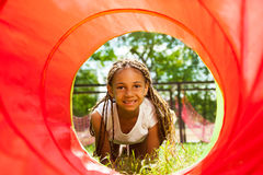 Black beautiful girl crawling though the tube Stock Images