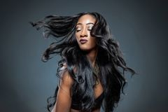Black woman with long luxurious shiny hair. Black beautiful woman with long luxurious shiny hair stock image