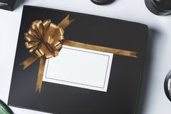 Black beauty box with golden ribbon and blank white branding mock up on light background, top view. Blog promotion. Fashion and royalty free stock photo