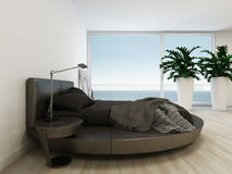Black bed against huge window with sea / ocean view Stock Image