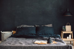 Black bedroom in loft style. Black stylish loft bedroom. Unmade bed with breakfast and reading on tray. Lamp and interior decor over blank blackboard wall with royalty free stock photography