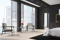 Black bedroom with two armchairs. Black bedroom interior with a white cover bed, two white armchairs, a wooden floor and a loft window. 3d rendering Stock Photo