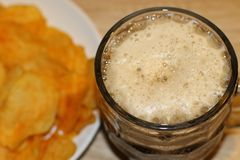 Foamy black beer and crispy chips stock image