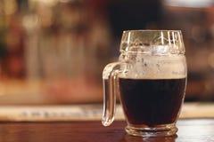 Black beer on wooden table. Half mug Black beer. Royalty Free Stock Photo