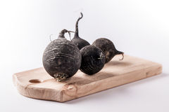 Black beet group on wooden board. Black beet group on wooden cutting board and white background Royalty Free Stock Image
