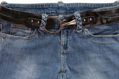 A black belt is in blue jeans. Stock Photo