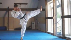 Black belt karate fighter training hight kick. Karate. Man in kimono doing high kick with his foot stock footage