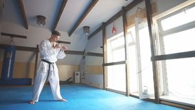 Black belt karate fighter training hight kick. Karate. Man in kimono doing high kick with his foot. Slow motion stock video footage