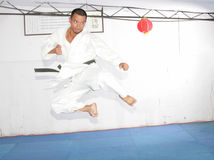 Black belt karate man jumping to give a high kick Stock Photo