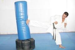 Black belt Karate man practicing in a sandbag Royalty Free Stock Photos