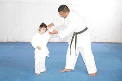 Black belt Karate teaching a little girl Stock Photography