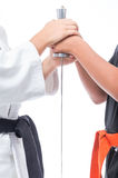 Black belt in martial arts that holds the hilt of the sword. Along with a student with orange belt Royalty Free Stock Images