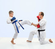 With black belt trainer teaches the athlete to beat kick leg on the simulator Royalty Free Stock Images