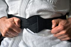 Black belt tying stock image