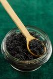 Black Beluga caviar in jar on a green fabric background Royalty Free Stock Image