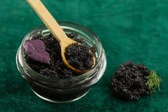 Black Beluga caviar jar on a green fabric background Royalty Free Stock Photography