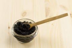 Black Beluga caviar jar on wooden background Royalty Free Stock Photo