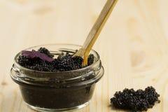 Black Beluga caviar jar on wooden background Stock Images