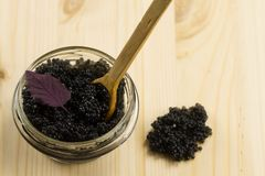 Black Beluga caviar  jar on wooden background Royalty Free Stock Photography