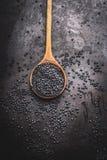 Black beluga lentil  seeds in wooden cooking spoon on dark rustic background Stock Photo