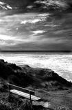 Black Bench. Bench by the ocean, black and white Royalty Free Stock Photography