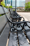 Black bench with artistic black railings and rain drops. Black bench with artistic black railings. Outside bench with black metal arm rests. Outdoor park Royalty Free Stock Image