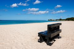Black bench on a beach in Barbados. Idyllic afternoon at the beach in Barbados Caribbean island: Nobody, white sand, clear turquoise water with waves and a Royalty Free Stock Image