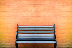 Black bench on brick wall. Black bench in front of variant color processed brick wall stock photos