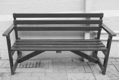 Black bench seat. Public bench seat - black painted wood stock photos