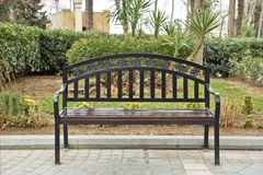 Black iron chair . Black bench on the street . Bench in Park on a background of brick green tree royalty free stock images