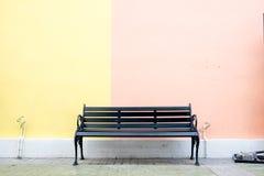 Black bench at yellow and pink wall at street Stock Images
