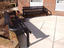 Black benches by brick building Royalty Free Stock Photography