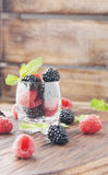 Black berries and raspberries in a glass cup Stock Images
