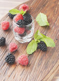 Black berries and raspberries in a glass cup Stock Photos