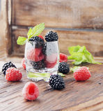 Black berries and raspberries in a glass cup Royalty Free Stock Images