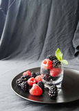 Black berries and raspberries in a glass cup Stock Photo
