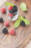 Black berries and raspberries in a glass cup. Black berries and raspberries in a glass black background, selective focus Royalty Free Stock Photo