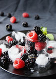 Black berries and raspberries in a glass cup Royalty Free Stock Image