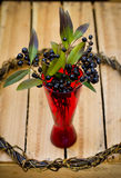 Black berries in red vase on wooden background Stock Photo