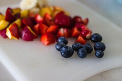 Black Berries With Sliced Fruits on White Plate Stock Photography