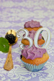Black berry cupcakes for a 30th anniversary. With purple frosting Stock Images