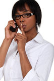 Black bespectacled woman. On the phone with finger before her mouth Stock Images